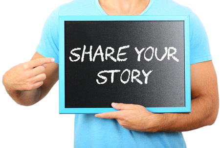 Man holding blackboard in hands and pointing the word SHARE YOUR STORY photo