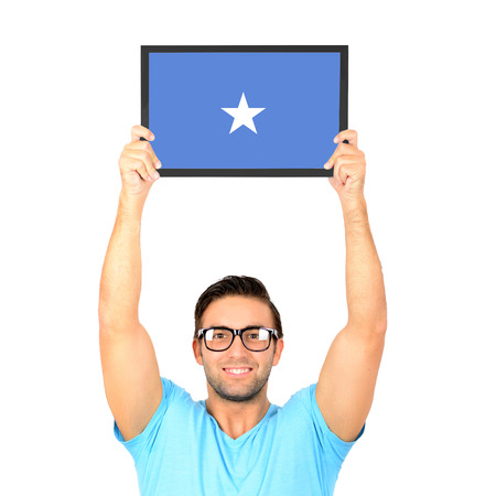 somalian flag: Portrait of a young casual man holding up board with National flag of Somalia
