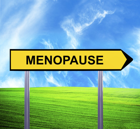 Conceptual arrow sign against beautiful landscape with text - MENOPAUSE photo