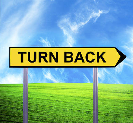 u turn sign: Conceptual arrow sign against beautiful landscape with text - TURN BACK Stock Photo