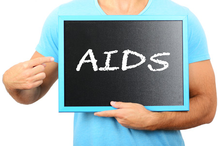 ilness: Man holding blackboard in hands and pointing the word AIDS Stock Photo