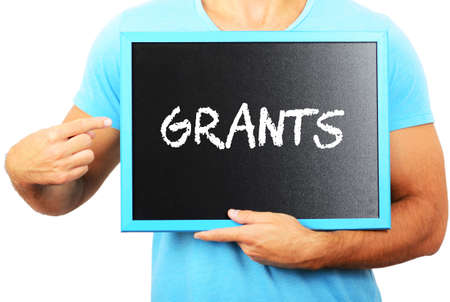 grants: Man holding blackboard in hands and pointing the word GRANTS Stock Photo