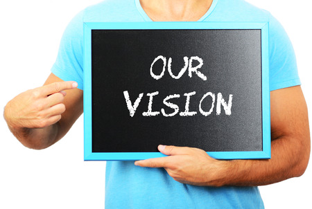 our vision: Man holding blackboard in hands and pointing the word OUR VISION