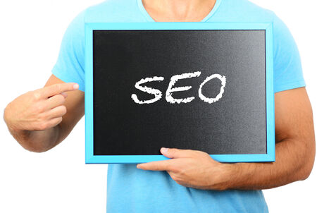 Man holding blackboard in hands and pointing the word SEO photo