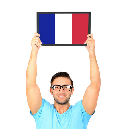 Portrait of a young casual man holding up board with National flag of France photo