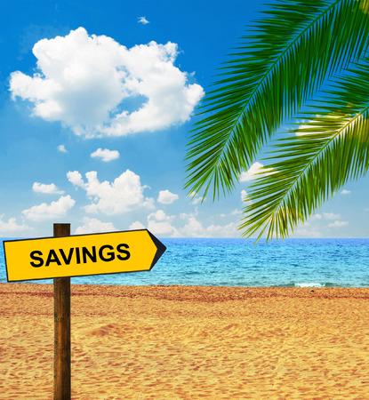Tropical beach and direction board saying SAVINGS photo