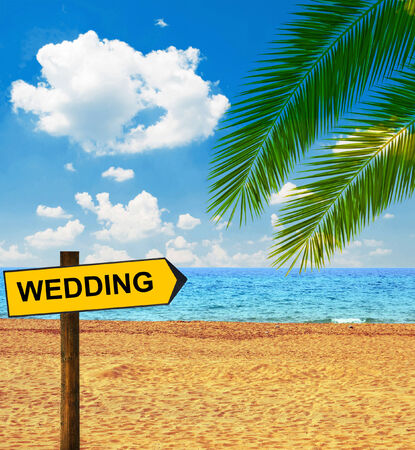 Tropical beach and direction board saying WEDDING photo