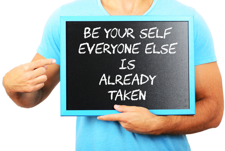Man holding blackboard in hands and pointing the word BE YOUR SELF EVERYONE ELSE IS ALREADY TAKEN