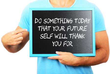 Man holding blackboard in hands and pointing the word DO SOMETHING TODAY THAT YOUR FUTURE SELF WILL THANK YOU FOR photo