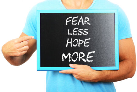 Man holding blackboard in hands and pointing the word FEAR LESS HOPE MORE Stock Photo