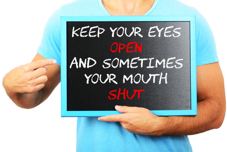 keep your hands: Man holding blackboard in hands and pointing the word KEEP YOUR EYES OPEN AND SOMETIMES YOUR MOUTH SHUT