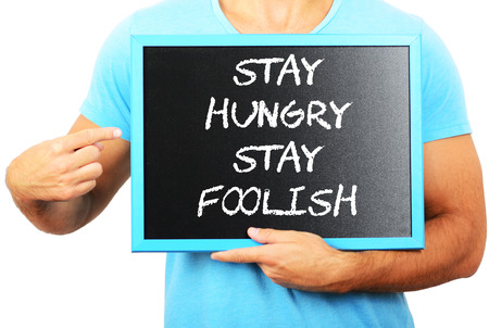 foolish: Man holding blackboard in hands and pointing the word STAY HUNGRY STAY FOOLISH