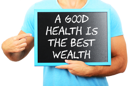 Man holding blackboard in hands and pointing the word A GOOD HEALTH IS THE BEST WEALTH photo