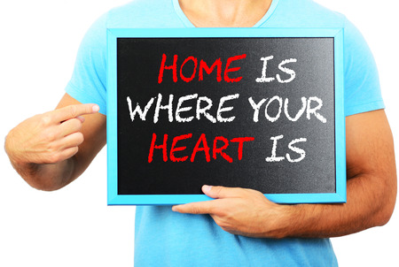 Man holding blackboard in hands and pointing the word HOME IS WHERE YOUR HEART IS photo