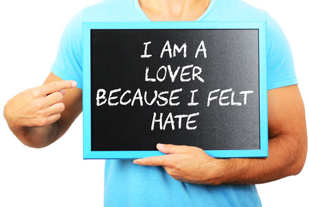 Man holding blackboard in hands and pointing the word I AM A LOVER BECAUSE I FELT HATE photo
