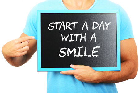 Man holding blackboard in hands and pointing the word START A DAY WITH A SMILE photo