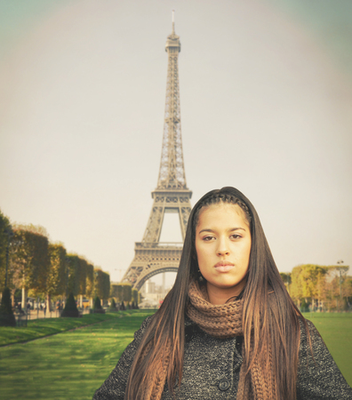 frenchwoman: Beautiful fashion model standing against Eiffel tower Stock Photo