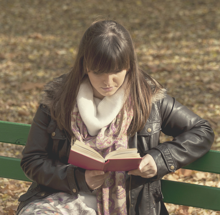 Beautiful woman sitting on a park bench and reading a book photo