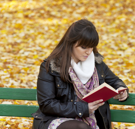 Beautiful young woman reads book photo