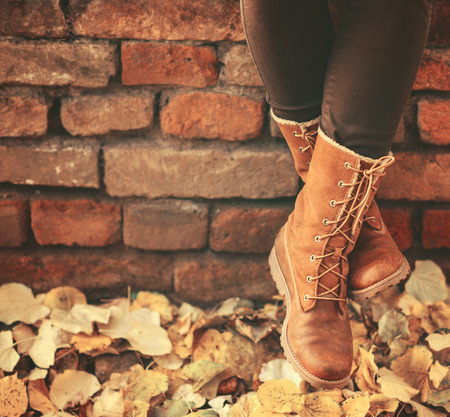 Conceptual image of legs in boots on the autumn leaves - Walking in nature