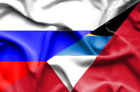 immigrant: Waving flag of Antigua and Barbuda and Russia Stock Photo