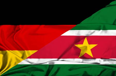 suriname: Waving flag of Suriname and Germany Stock Photo