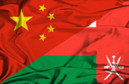 oman background: Waving flag of Oman and China Stock Photo