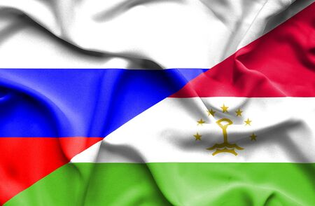 tajikistan: Waving flag of Tajikistan and Russia Stock Photo