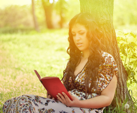 Woman reading book leaned against tree photo