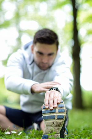 sportsman: Handsome sportsman stretching outdoors Stock Photo