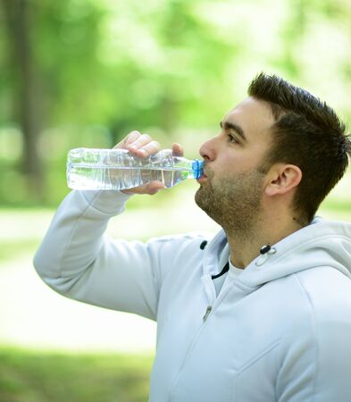 replenish: Fit young sportsman drinking water from plastic bottle after workout in outdoor park