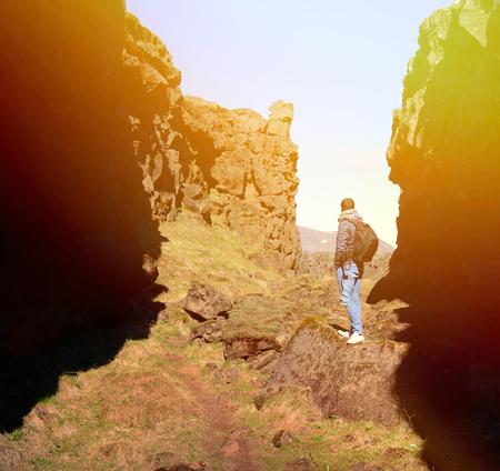 mochila de viaje: Individuo con una mochila de viaje en la cima de una roca Foto de archivo