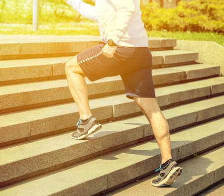 foot steps: Practice - Close up of young man running up the stairs Stock Photo