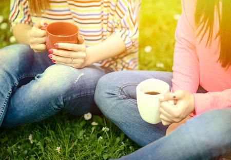 taza de café: Las mujeres jóvenes que beben el café en el parque y disfrutando día de verano
