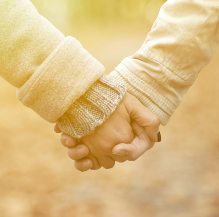 holding hands while walking: Closeup of couple holding hands while walking in park