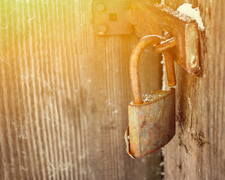 oxidize: Old padlock on wooden door