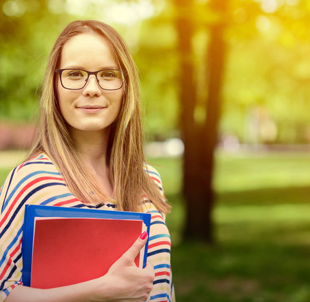 campuses: Young happy student woman with the book in her hands is standing and smiling in the university park Stock Photo