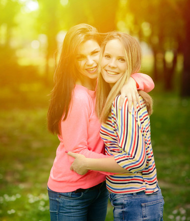 teenage girls: Two young girl friends together in hug at park