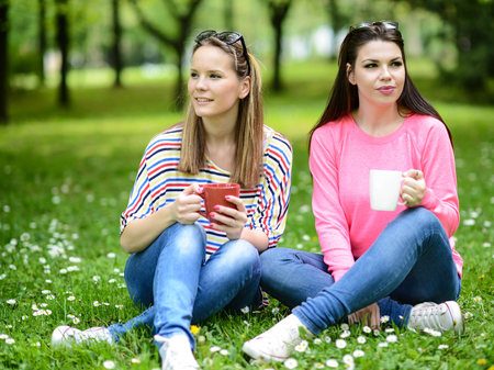 shallow dof: Young women drinking coffee at park and enjoying summer day