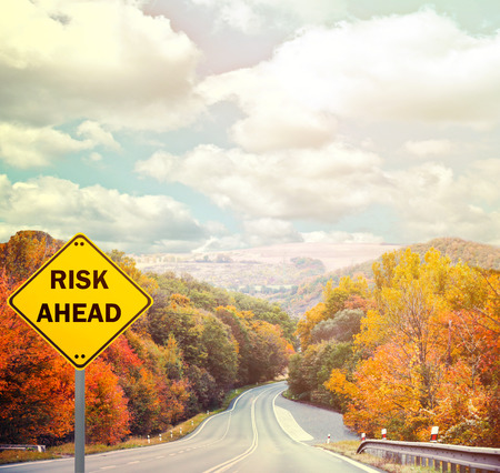 risk ahead: RISK AHEAD sign against road - Business concept