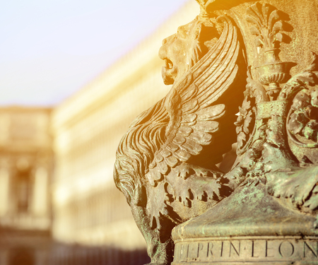 leon con alas: Estatua del león alado fragmento arquitectónico de Venecia. Detalle de león alado en un asta de bandera en la Plaza de San Marco, Venecia, Italia Foto de archivo