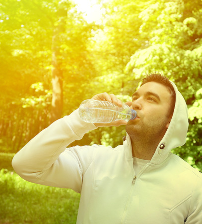energize: Fit young sportsman drinking water from plastic bottle after workout in outdoor park