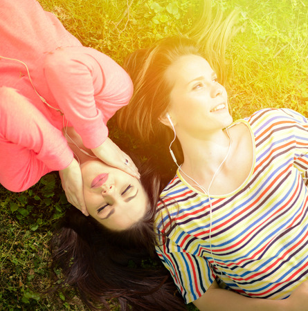 two persons only: Two girl friends listening to music while lying on grass during summer day