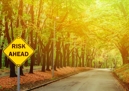 risk ahead: RISK AHEAD sign against road in green forest - Business concept Stock Photo
