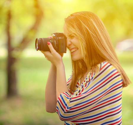 freetime: Portrait of beautiful laughing brunette girl taking photos at park Stock Photo