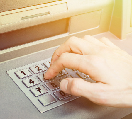 cash on hand: Hand entering PIN numbers on ATM bank machine