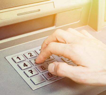 automatic transaction machine: Mano de introducir los n�meros de PIN en cajero autom�tico ATM Foto de archivo