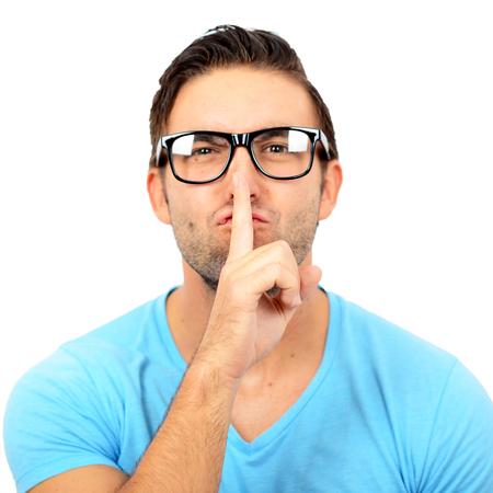discreto: Retrato de hombre con gesto de silencio contra el fondo blanco
