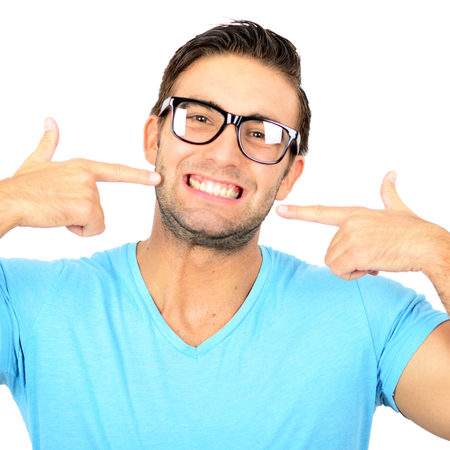 dientes sanos: Retrato de hombre guapo poitning a su sonrisa saludable o los dientes contra el fondo blanco