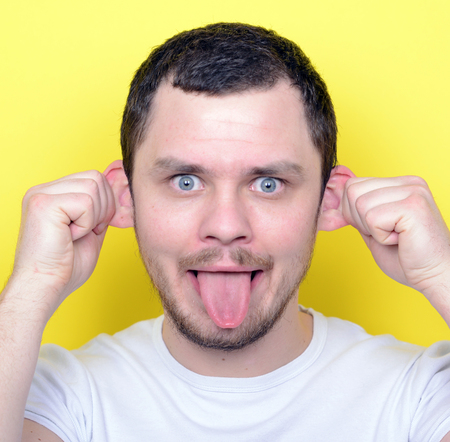 weirdo: Portrait of man with funny face against yellow background